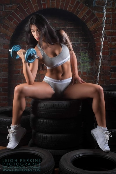 model lit by three lights using dumbbells