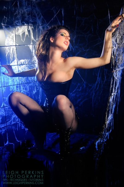 Model October posing in a cobweb infested studio set with blue light.